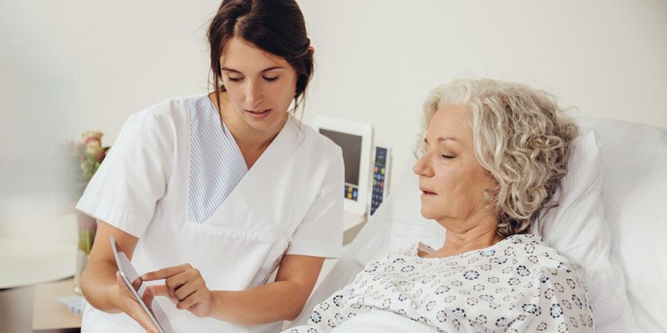 Krankenschwester erklärt Patientin etwas auf dem Tablet