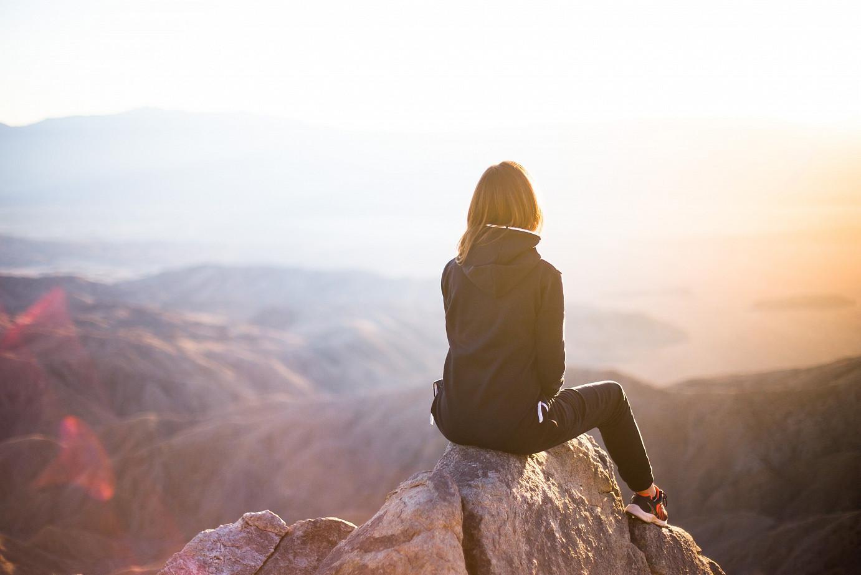 Eine Frau auf einem Berg blickt in die Ferne. Auch das Leben mit Krebs ermöglicht viele schöne Momente