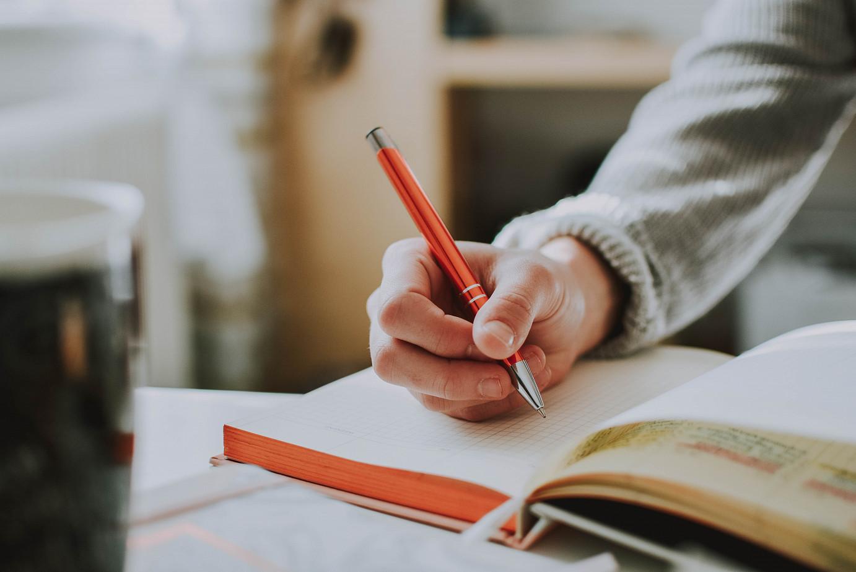 Eine männliche Hand, die in ein Buch schreibt