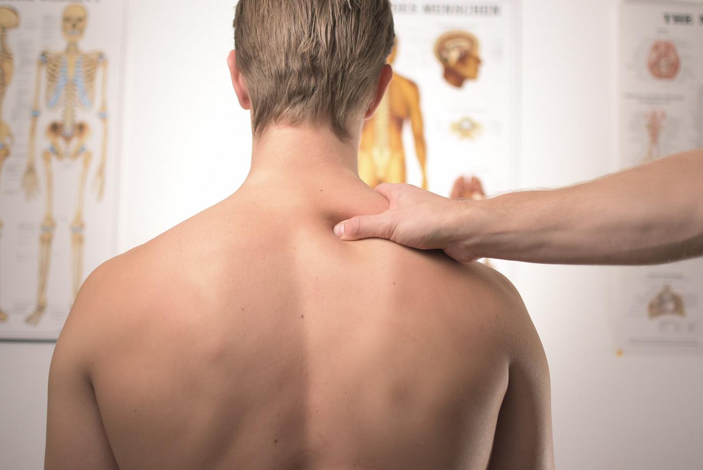 Mann von hinten in einem Arztzimmer, der ein Schulterklopfen vom Arzt bekommt.