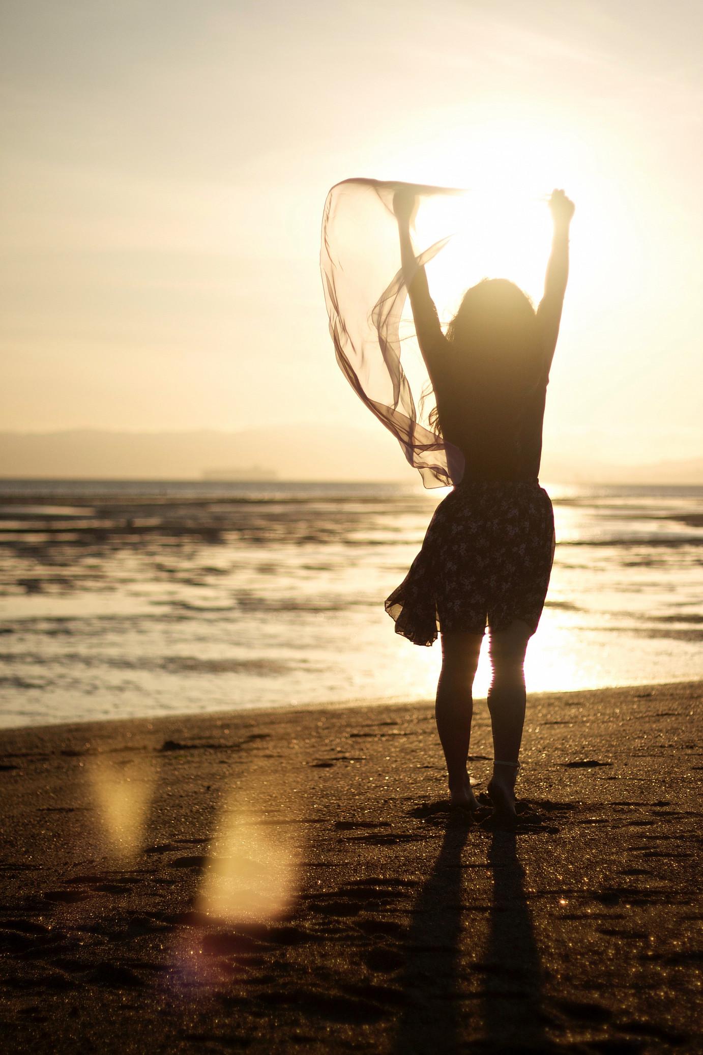 Frau beobachtet Sonnenuntergang am Meer